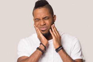 Man holding hands to jaw experiencing wisdom tooth pain